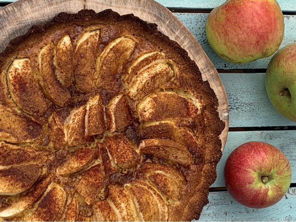 æbletærte på fad med rødgrønne æbler på bordet