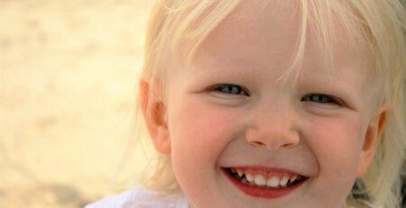 en pige smiler og viser sine tænder