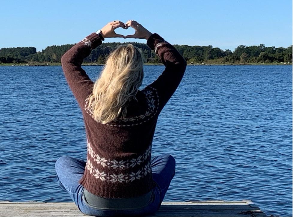 Marie Louise sidder på en badebro og kigger ud over vandet og folder sine fingre som et hjerte
