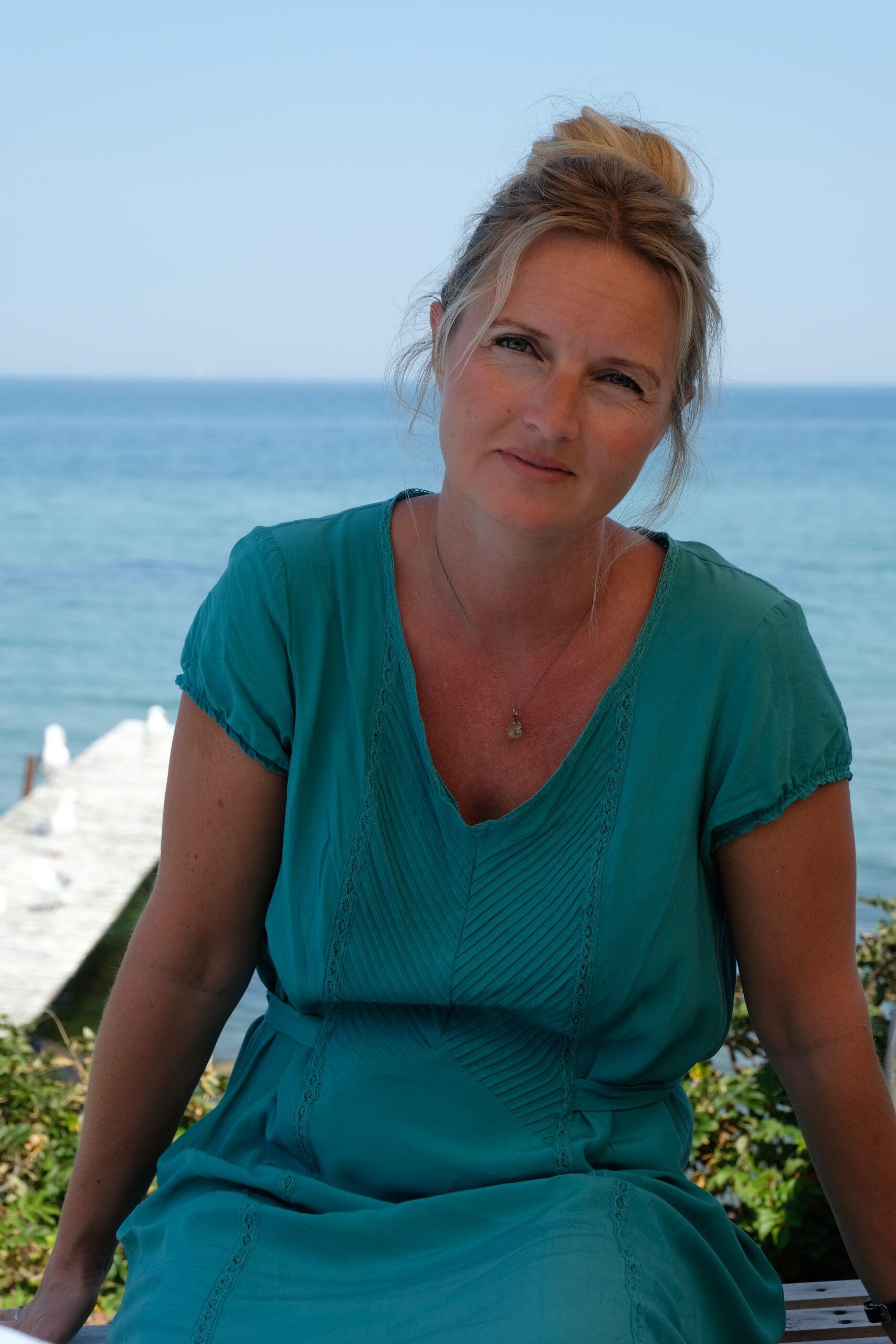 Marie Louise sidder på bænk med havet i baggrunden
