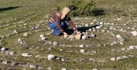 Marie Louise rører ved nogle sten der ligger i spiralformet cirkler