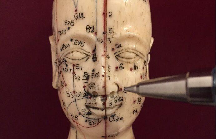 en ansigtsfigur med aftegnet akupunkturpunkter