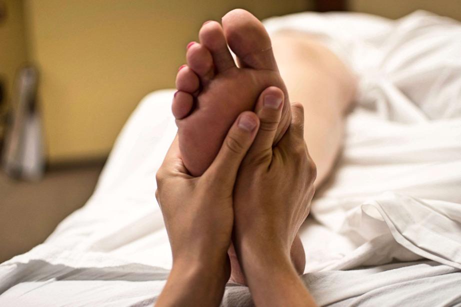en kvinde får zoneterapi på fødder